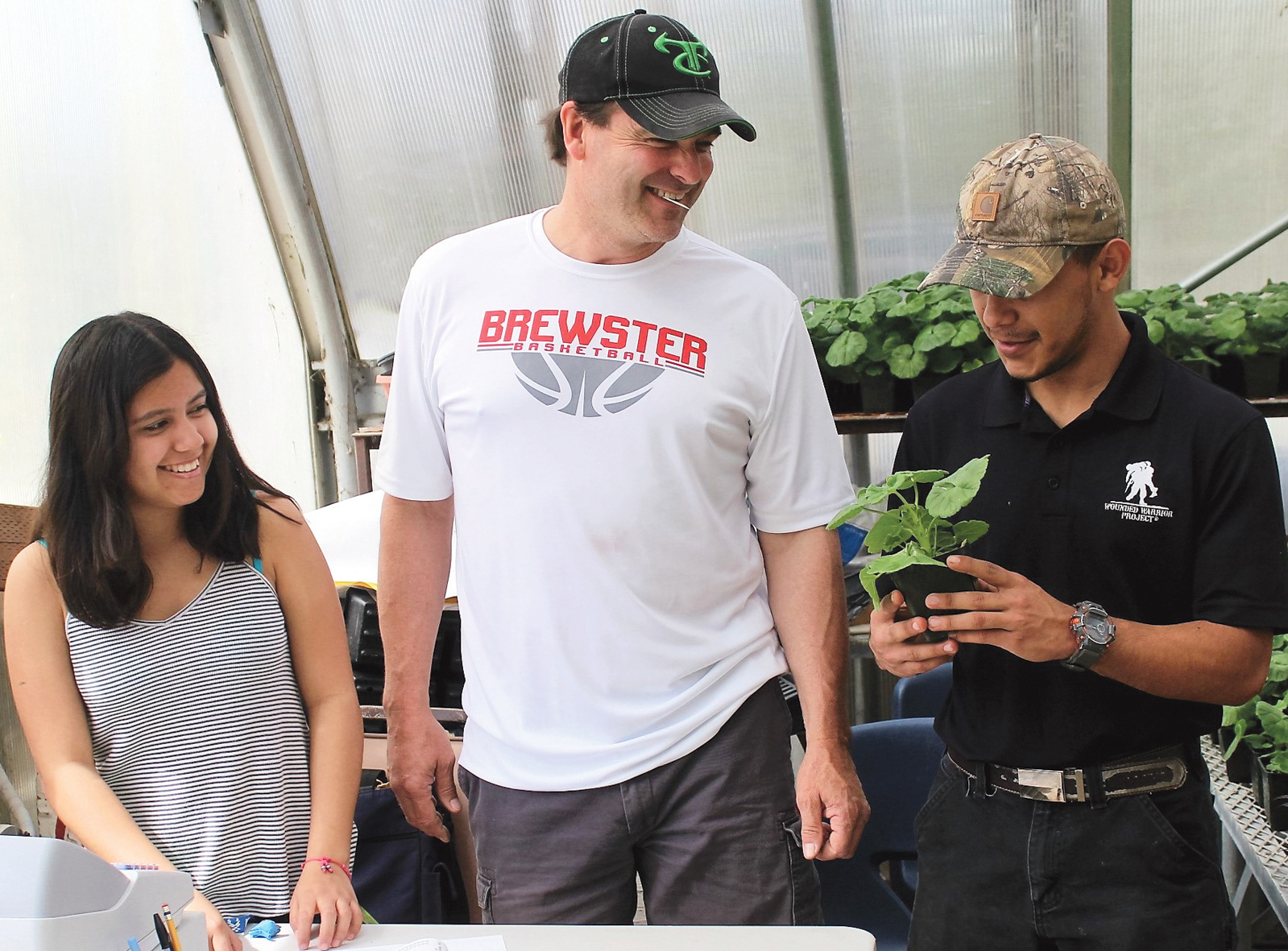 Brewster High School students Melissa Corrales and Erick Pamatz man the school greenhouse along with Ag advisor Todd Dezellem during last weekend's spring plant sale. The three also took a selection of plants to the Pateros Arbor Days celebration last Friday.