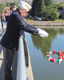American Legion Area Three Commander, Denny Pittman, releases a wreath into the Columbia River from the Bridge Street Bridge in honor of Navy and Coast Guard veterans.