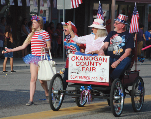 Ron Statler, at the wheel of his replica 1904 Oldsmobile with passenger, Carol Sivak, promoting the Okanogan County Fair.
