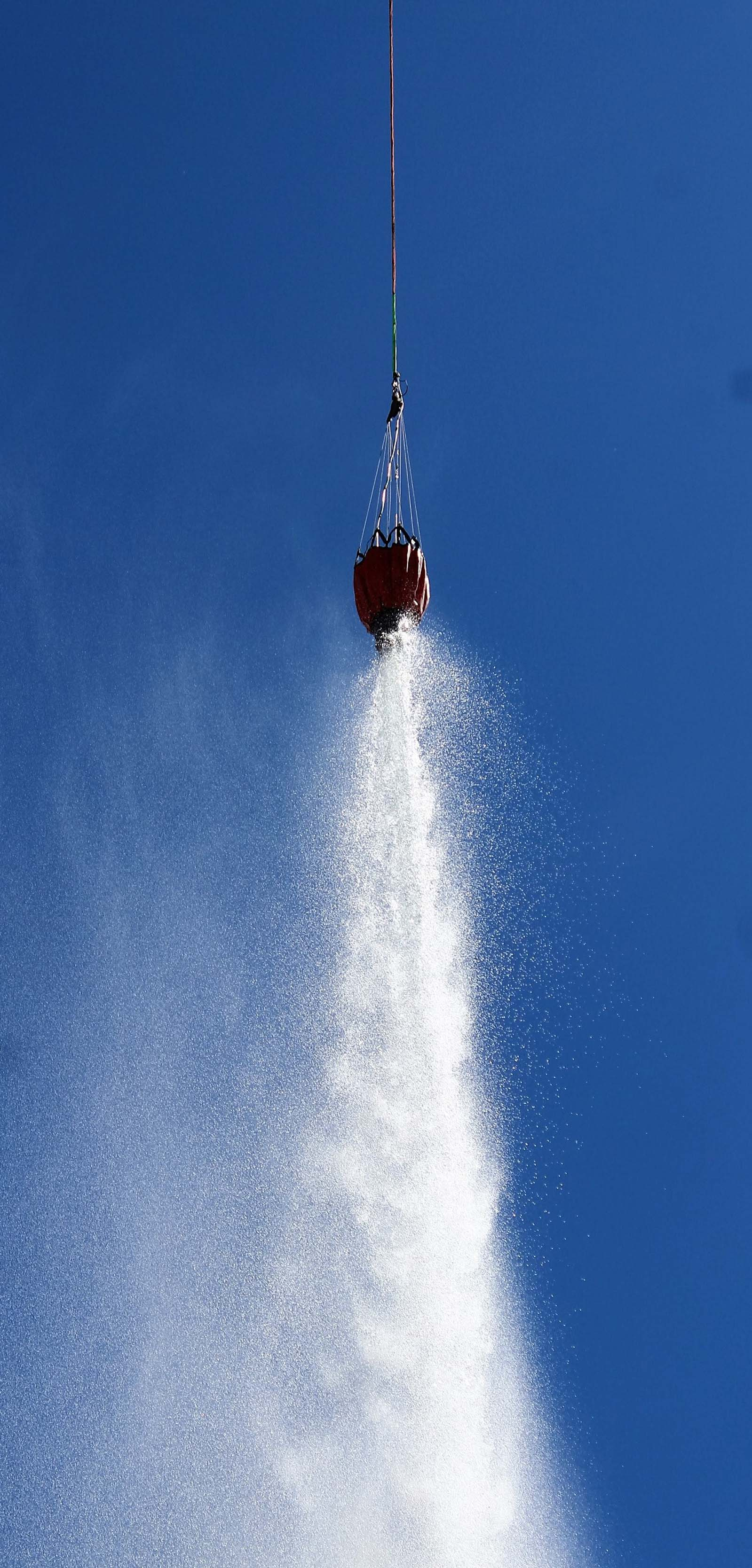 A helicopter water bucket drops a load of water along a fire line.