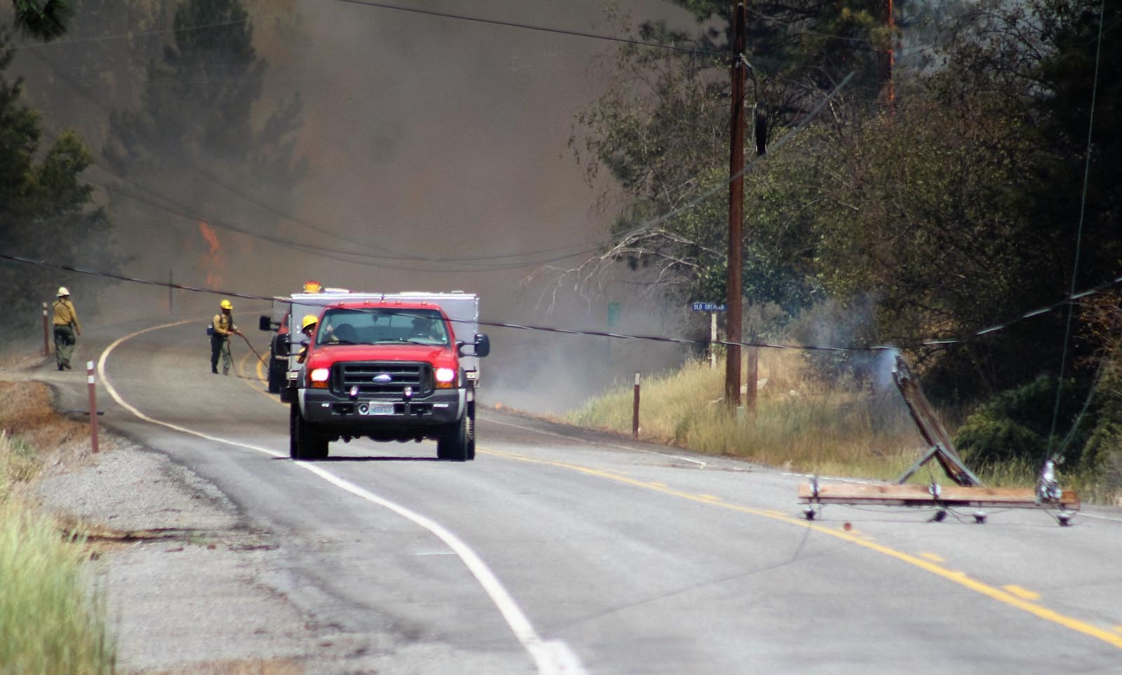 Flames burned through and toppled a power pole before jumping, seen in the background, to the west side of Highway 153.