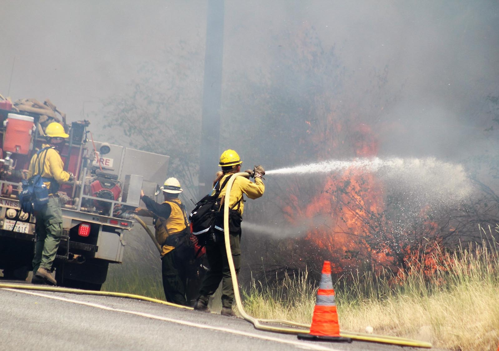 Two hoses from a DNR pumper target flames close to the highway.