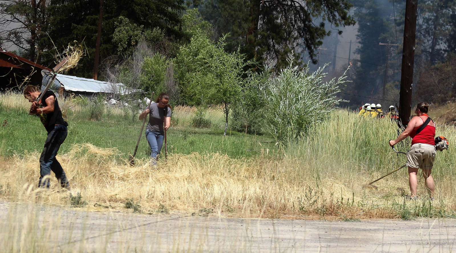 Residents just across the highway from the growing fire use hand and power tools to knock down dry and flammable weeds and grass