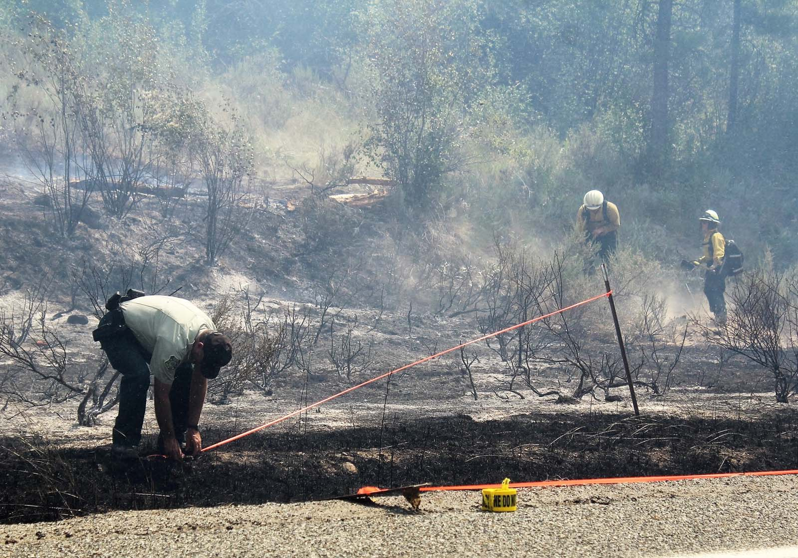 A Forest Service investigator adds more fire scene tape to the suspected ignition area.