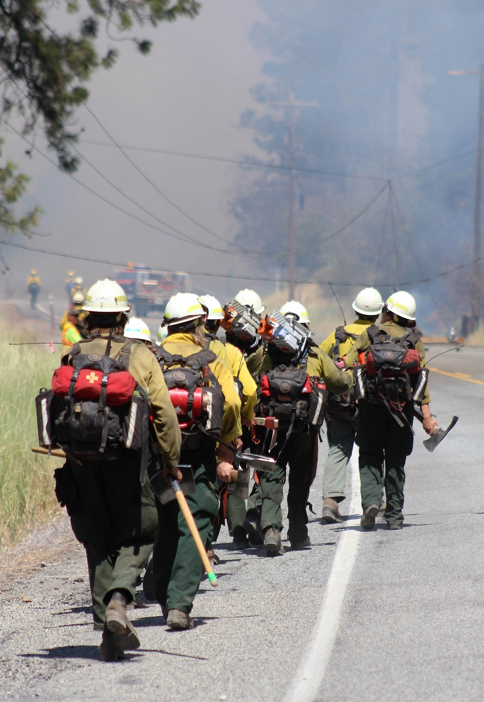 Firefighters move out along the west side of Highway 153 shortly after flames crossed the road north of their march.