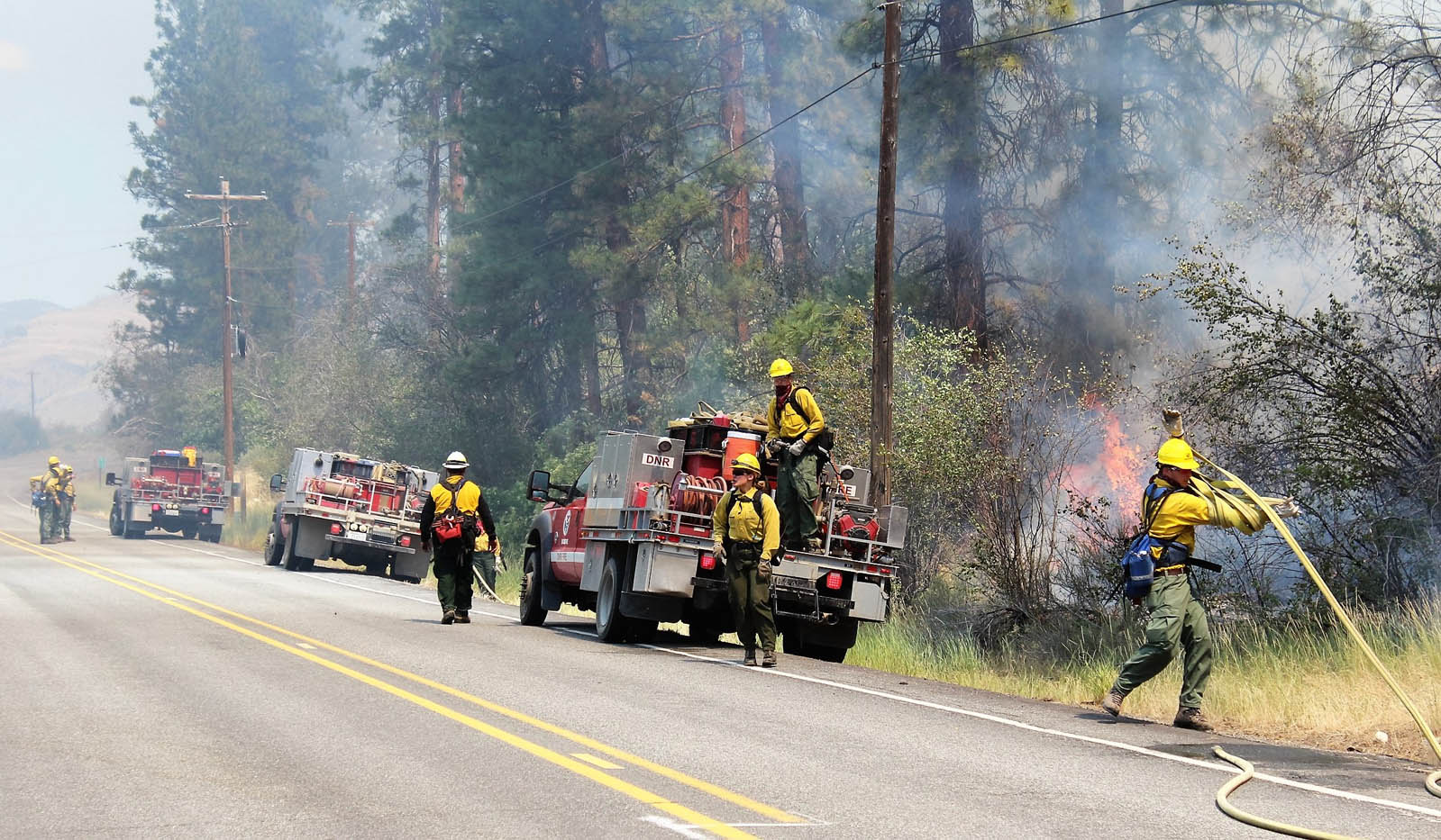 Three DNR fire rigs stay close to the roadside flames as they more north along Highway 153.