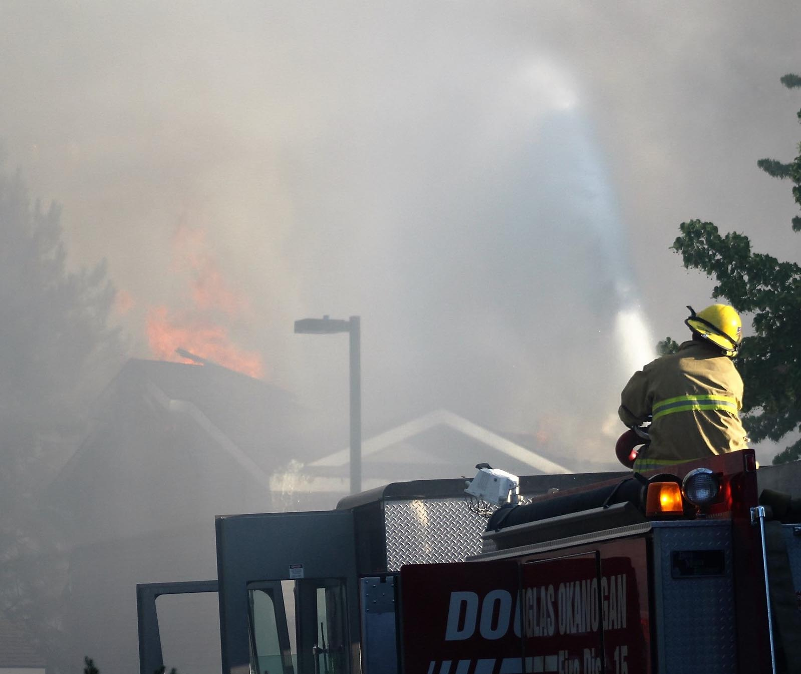 Flames can be seen on the roof of an apartment building in front of a firefighter manning the water cannon.