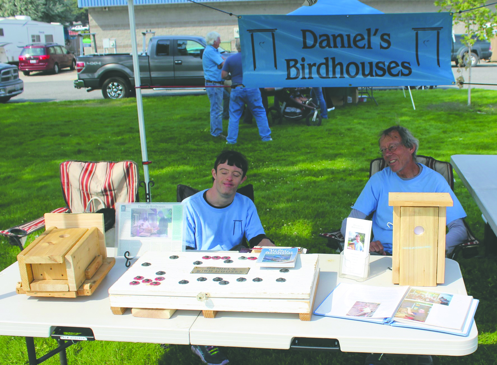 Daniel Anderman, left, with his father, Paul, came all the way from Leavenworth to display Daniel's hand-fashioned birdhouses. The box-like device seen in the foreground is actually a drilling template that Daniel uses to precisely cut the holes in the wood sections used to build the boxes.
