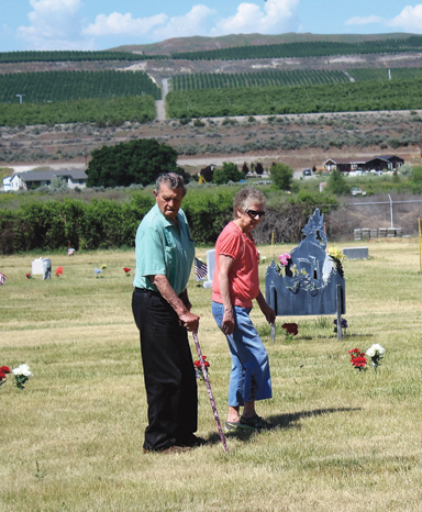 Brewster residents, Don Reese and Rosemary Harder pay their respects at the Fort Okanogan Memorial Cemetery in Monse.